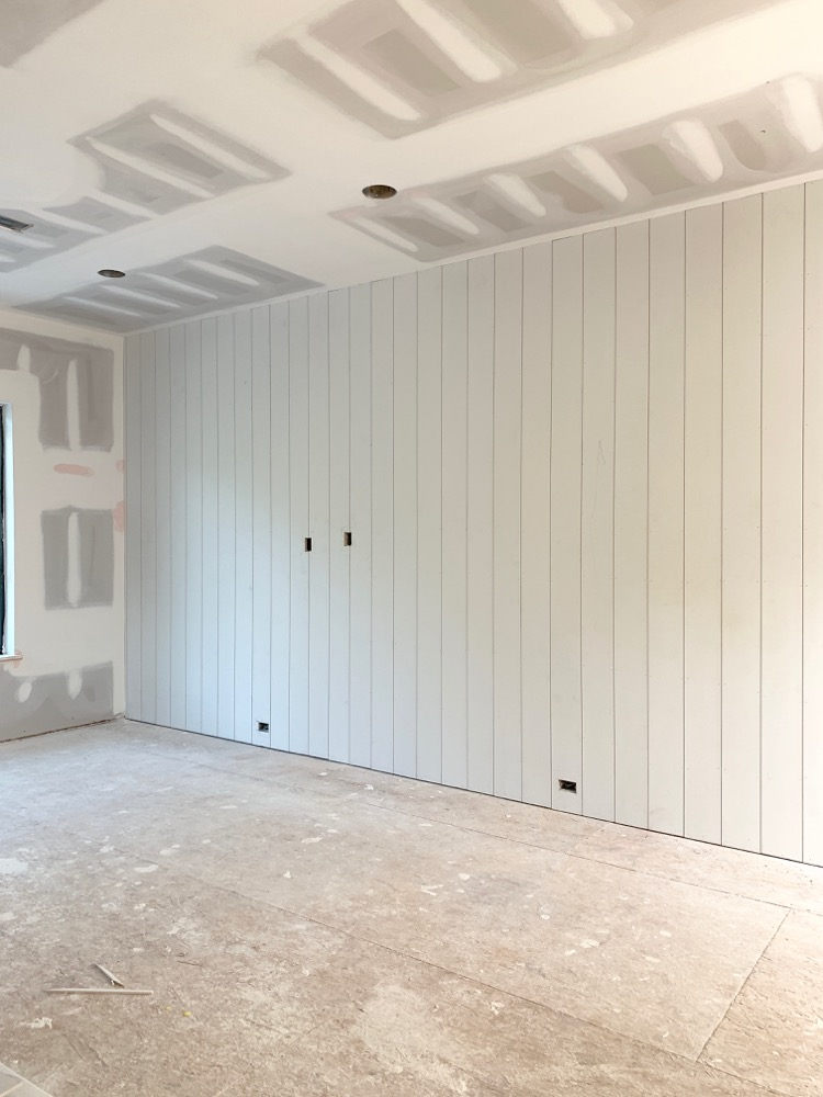 large game room under construction with vertical shiplap wall