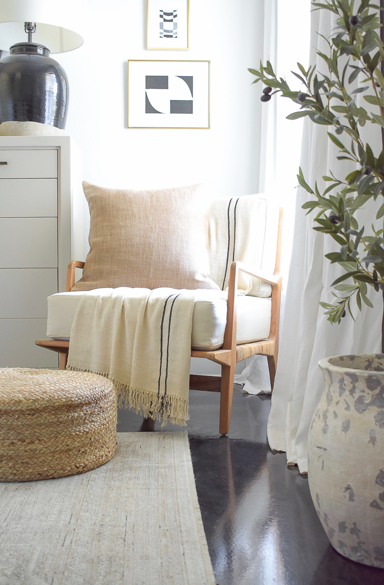 Boho chic chair in this fall neutral layered bedroom