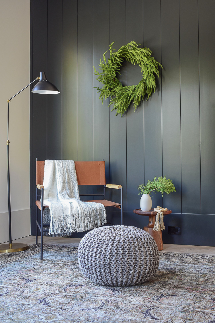 Modern leather chair, black vertical shiplap wall, olive charcoal loiloi rug from Joss & Main