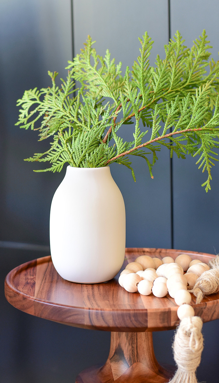 modern vase styled with wooden beads on side table