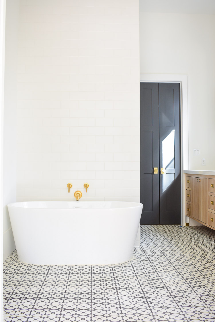 Free standing tub, black and white cement tile, white subway tile wall behind tub