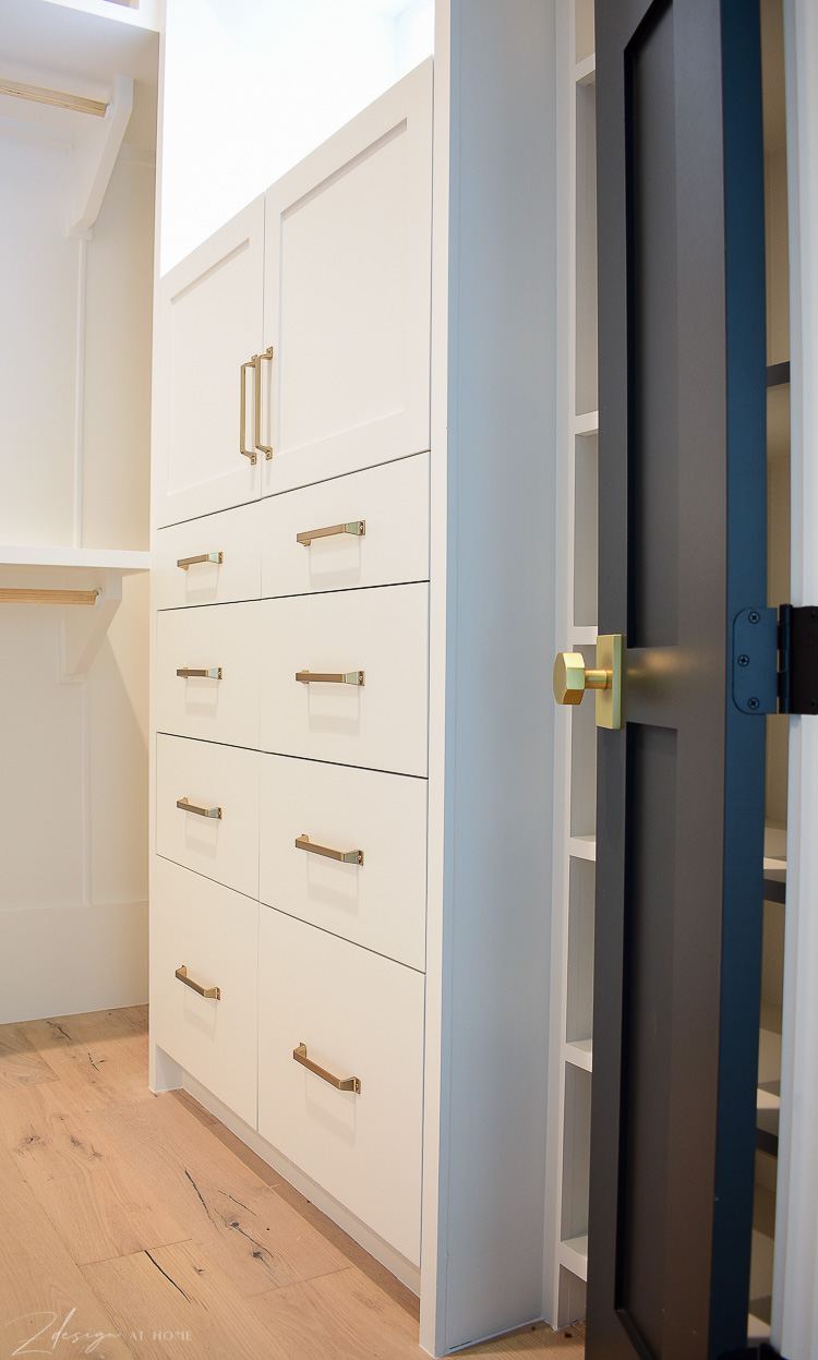 white cabinets in custom closet with brass hardware