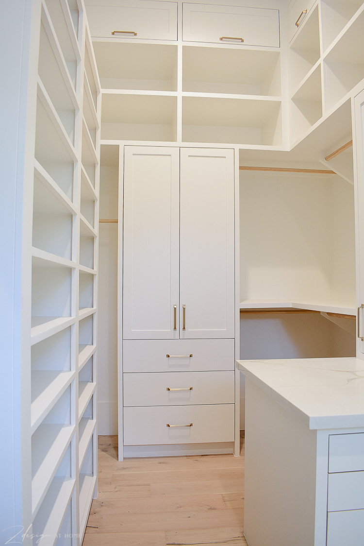 White cabinets in closet with brass hardware, closet design