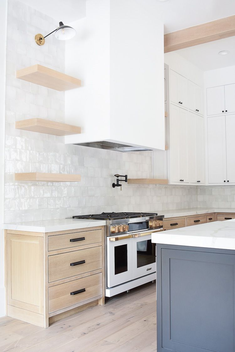 Kitchen design white oak cabinet, zellige tile, white range brass fittings
