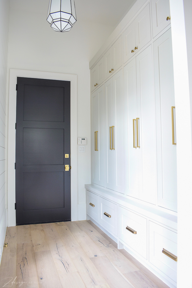 Mudroom with agreeable gray cabinets and modern brass hardware, white oak floors