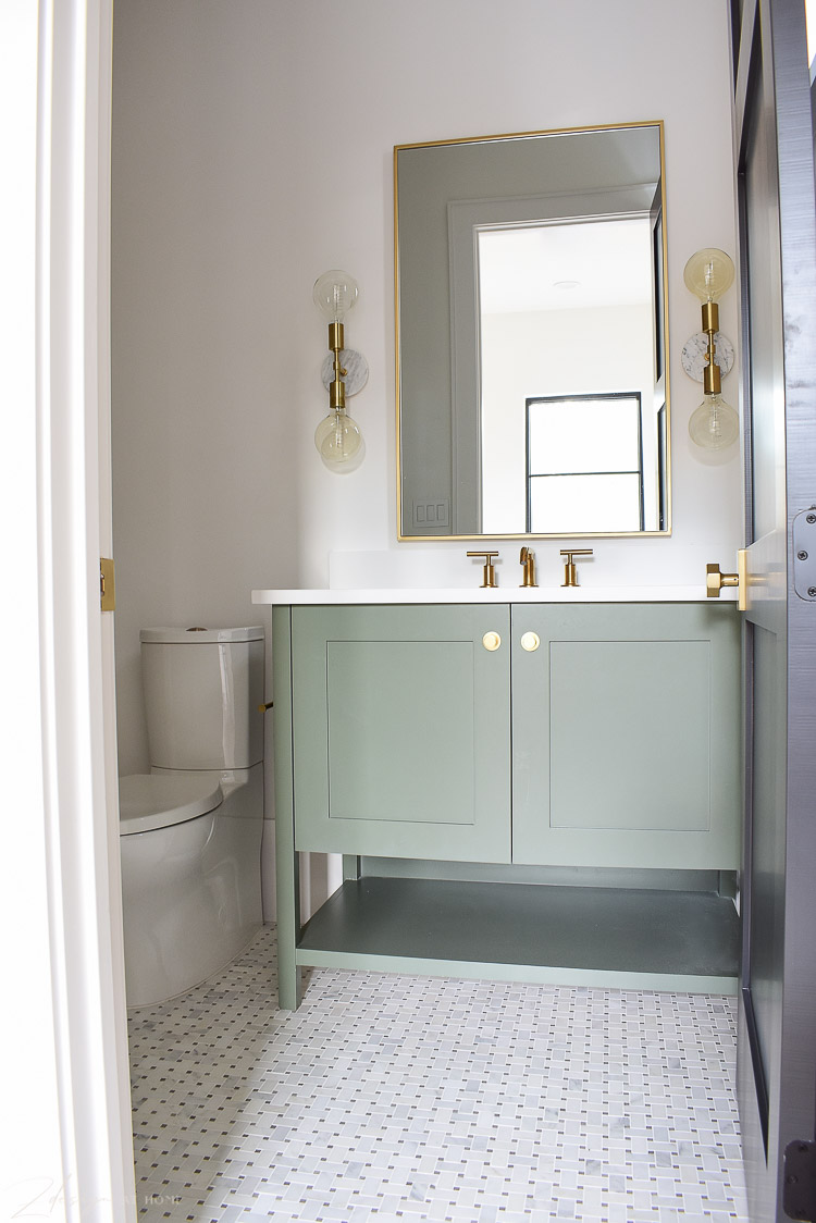 Bathroom with basketweave marble floors, green vanity and gold accents