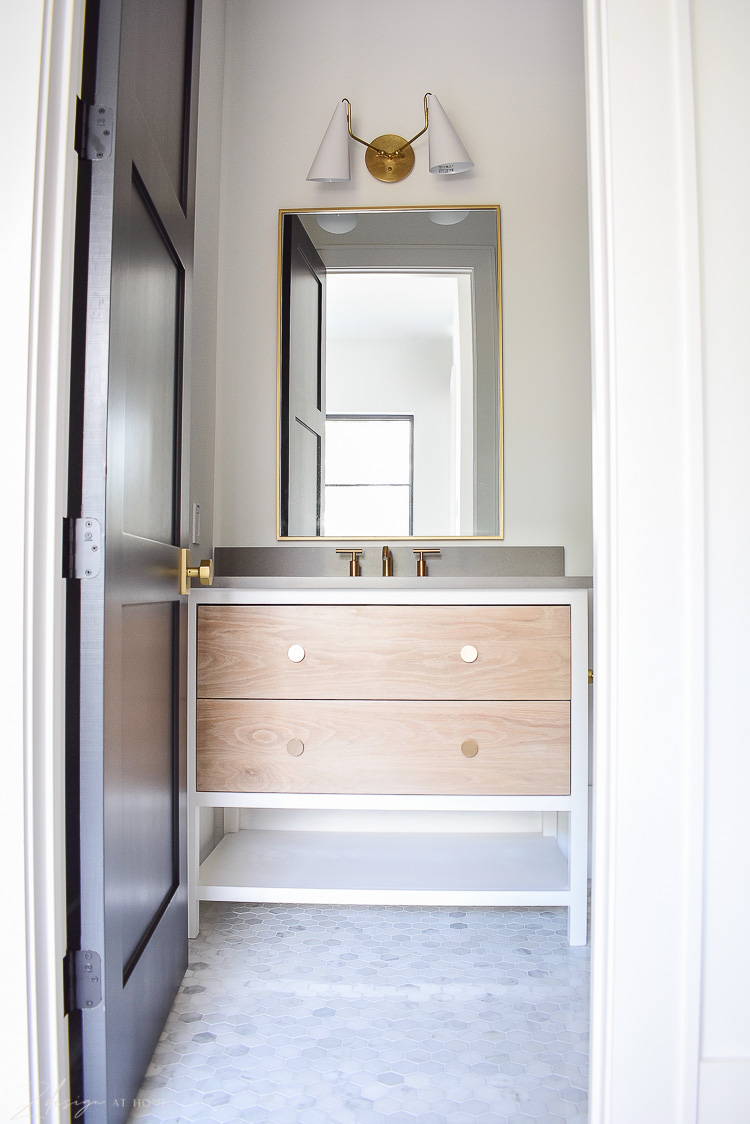 bathroom with two tone vanity white and white oak, gray countertops and brass accents