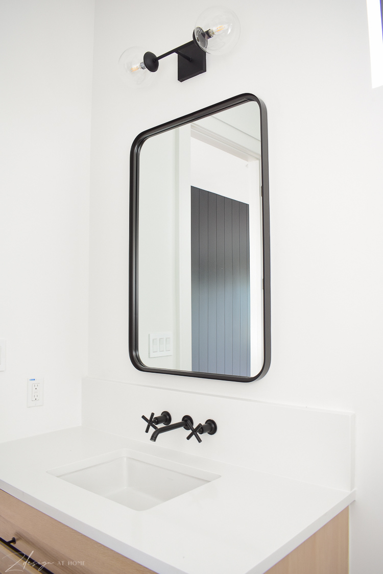 Studio Magee black metal mirror, kohler purist wall mount faucet in black, black double globe sconce