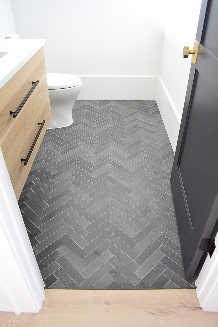 black, charcoal gray herringbone tile floors in powder bath