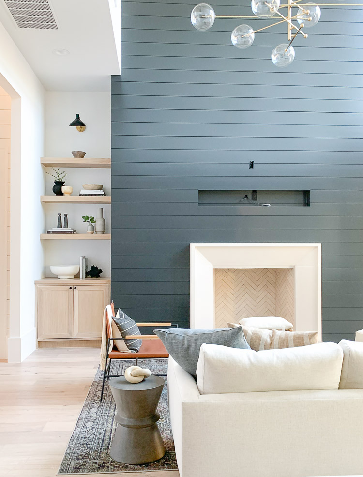 living room with black shiplap fireplace wall and white oak styled shelves
