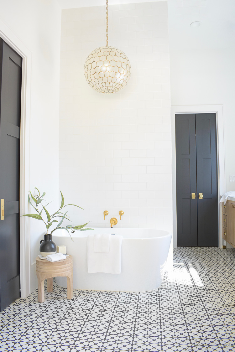 Joss & Main Spring Edit - wooden stool styled beside free standing tub in black and white modern elegant bathroom