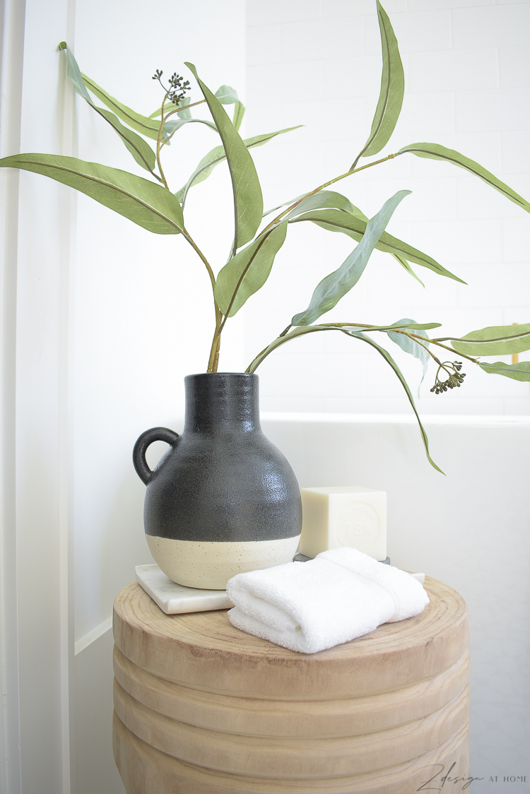 black two tone pottery vase with green stem on stool styled in front of tub - beautiful black and white modern bathroom