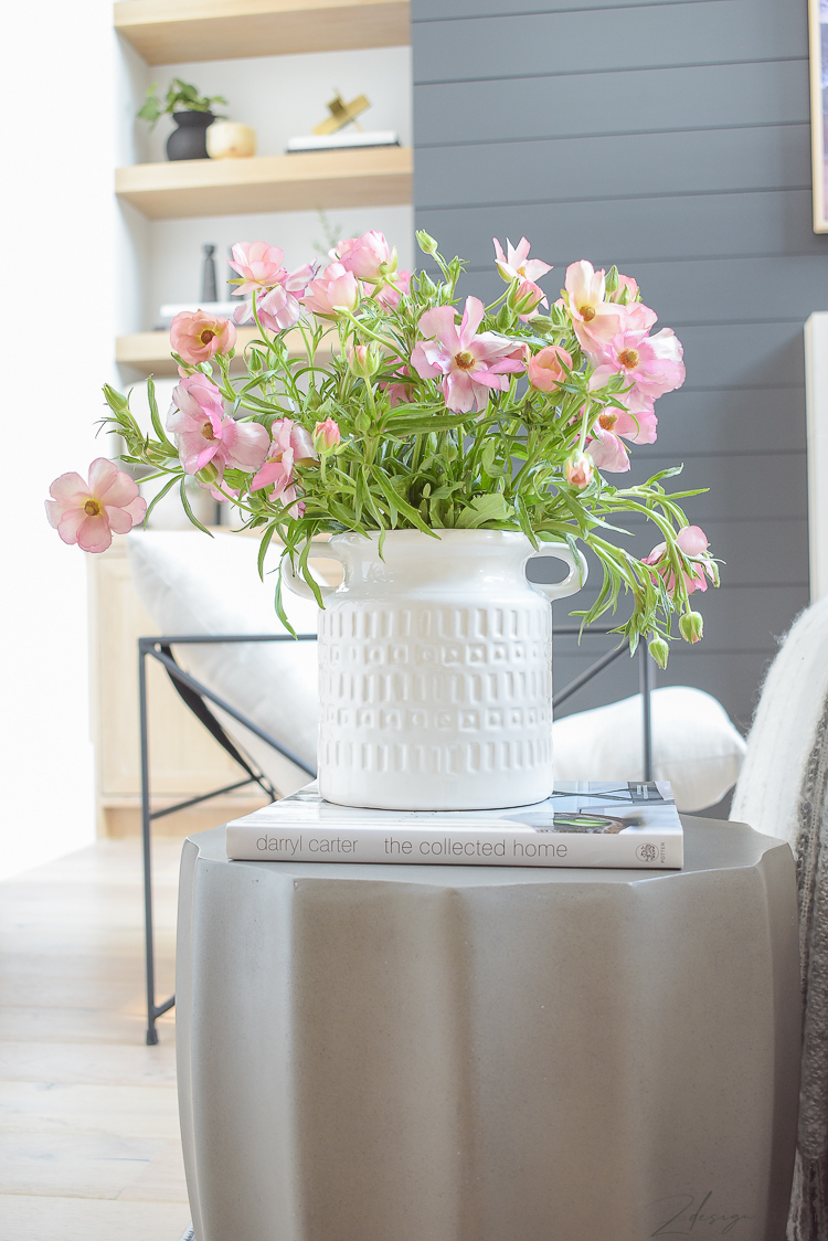 pink spring flowers in white vase on concrete side table