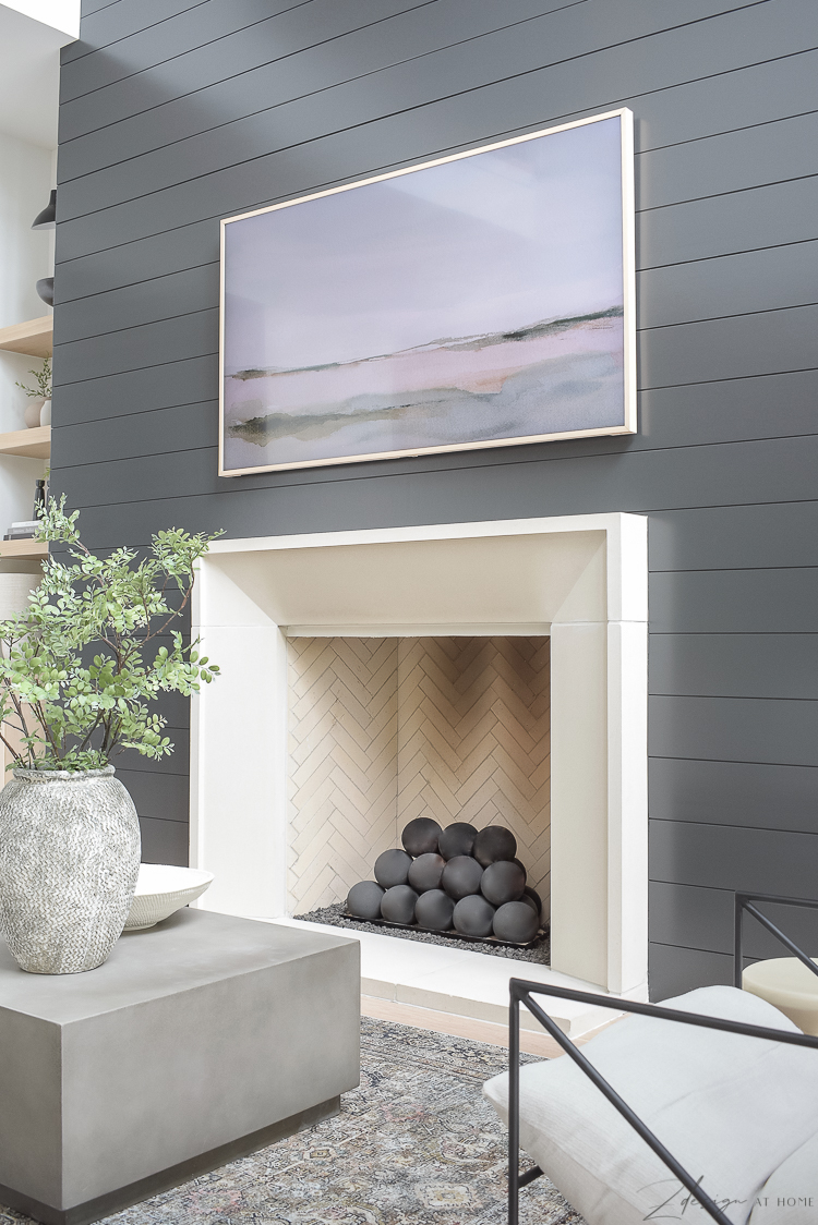 isokern fireplace with frame tv and black shiplap wall