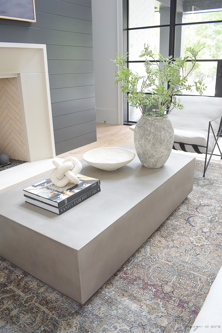 concrete coffee table with modern home decor accessories and black shiplap fireplace