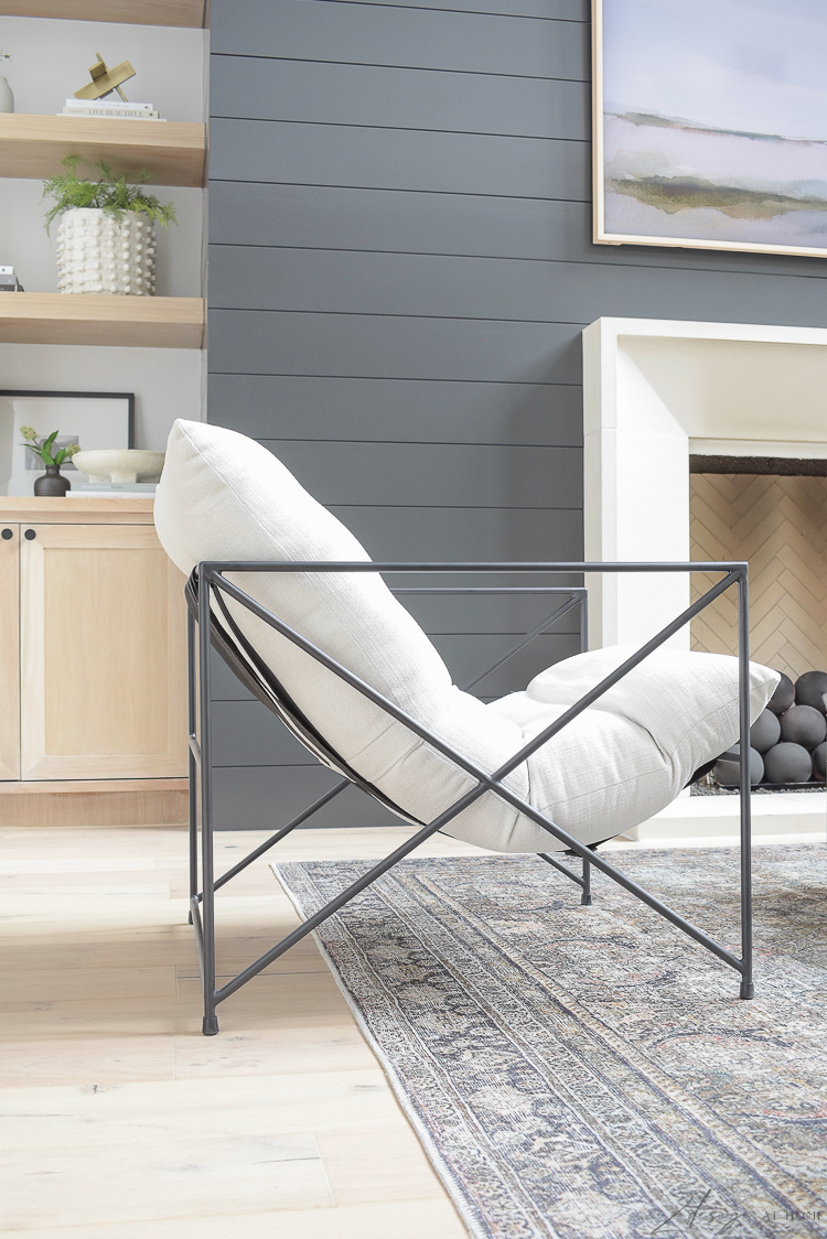 wayfair metal barracks accent chair with cream colored cushion in front of black shiplap fireplace wall