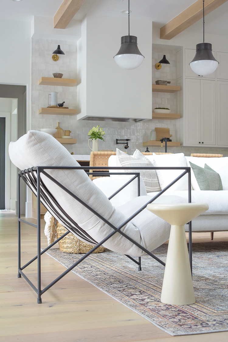 Concrete nesting tables next to modern metal side chair in transitional modern living room