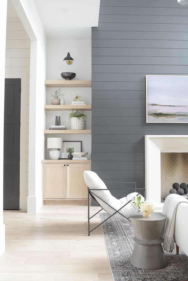 white oak shelves decorated in modern living room with black shiplap fireplace
