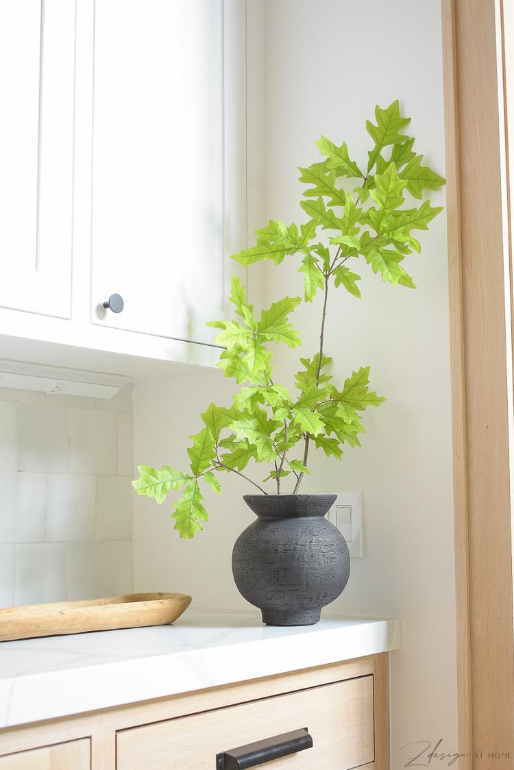 black vase with oak stem in white oak kitchen