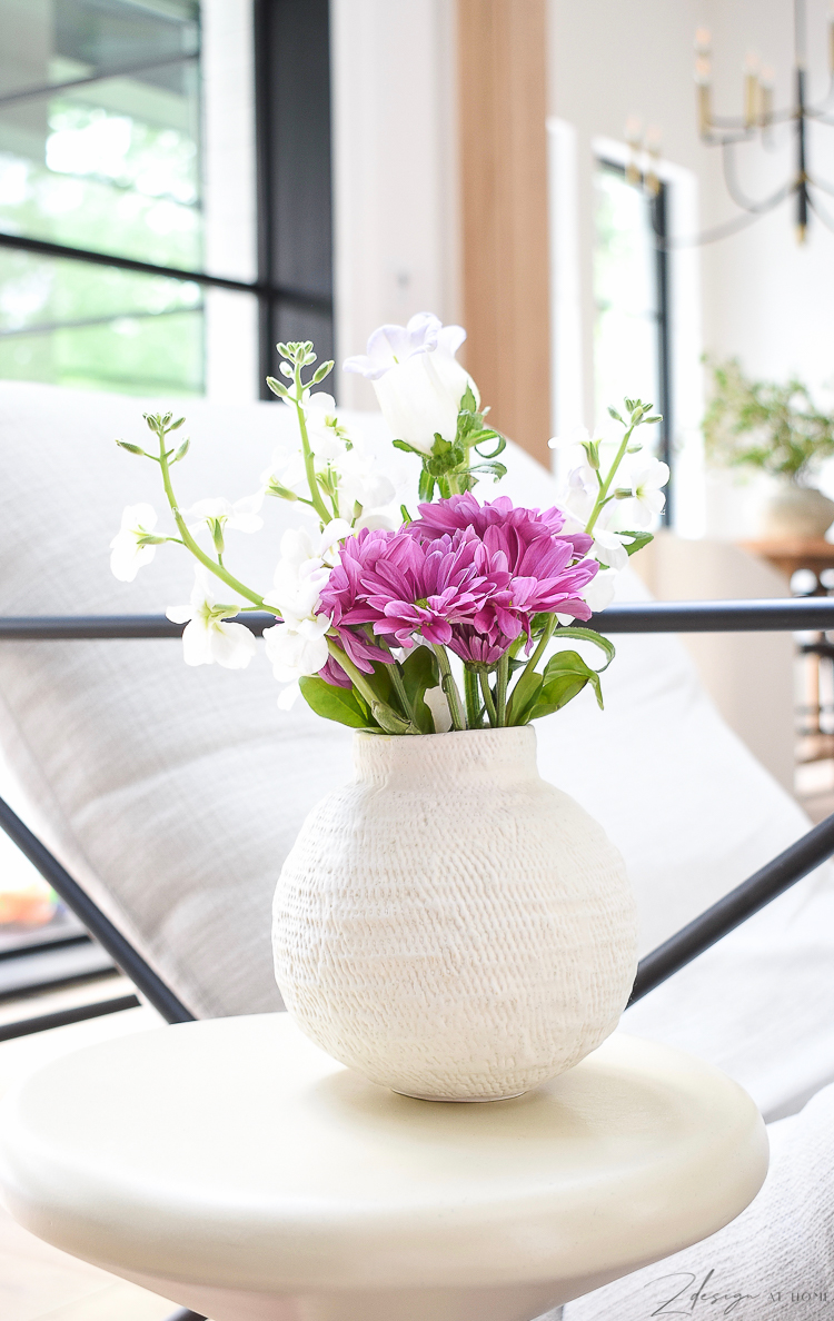 Small white bud vase with spring flowers