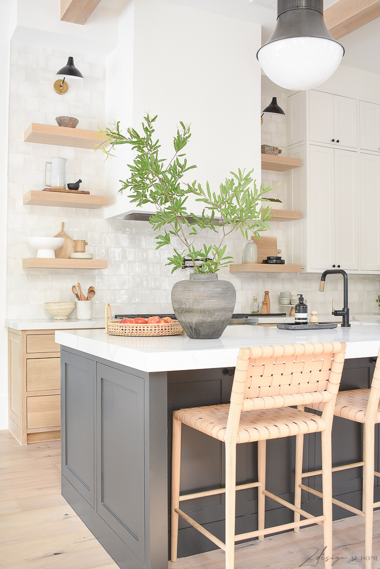 transitional modern kitchen with vintage inspired vase on counter. white oak cabinets, black island white uppers with white oak shelves