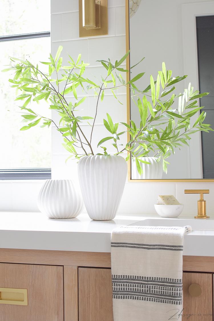 pair of white ribbed west elm vases on bathroom countertop