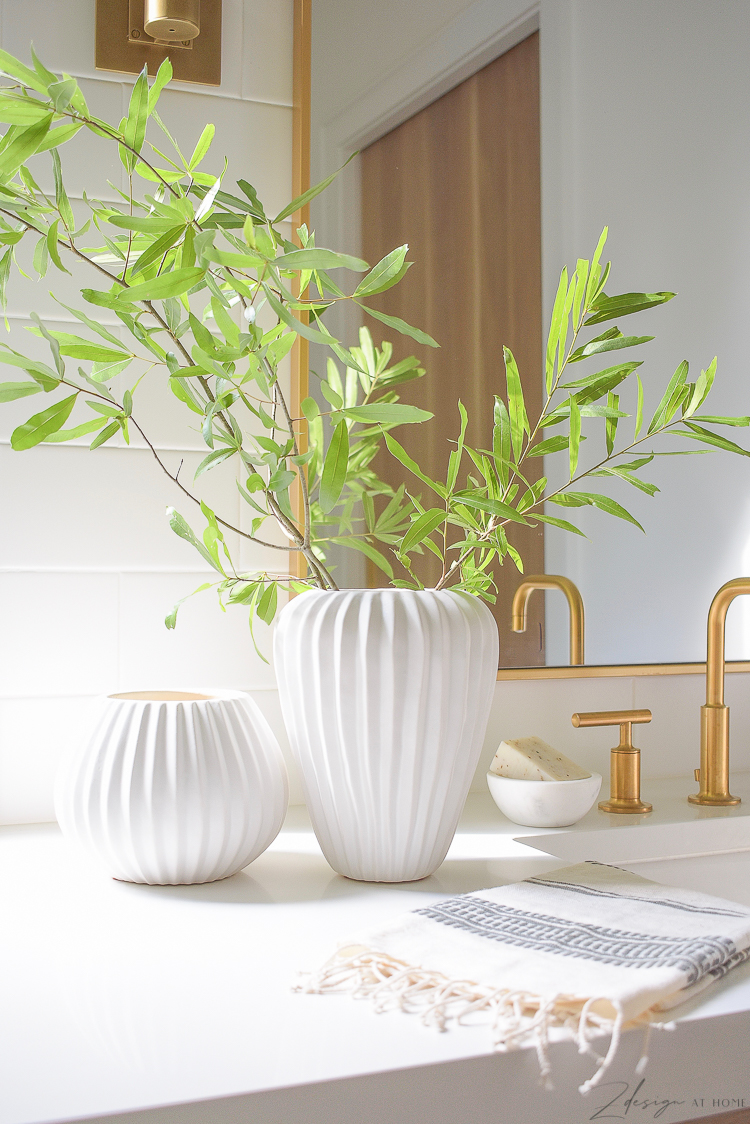 pair of white ribbed vases on bathroom countertop