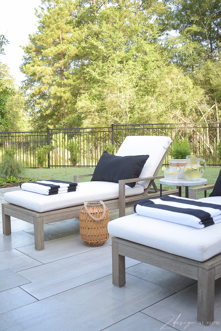 black and white striped beach pool towels, black lumbar pillow on outdoor pool lounger