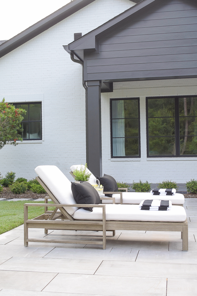 black and white outdoor decor - loungers with striped pool towels, black and white house pool area