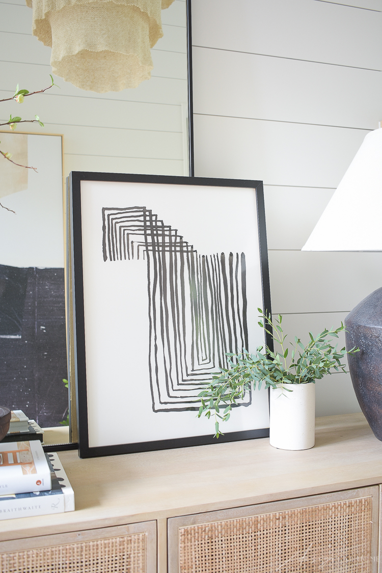Minted art leaning again mirror on console table