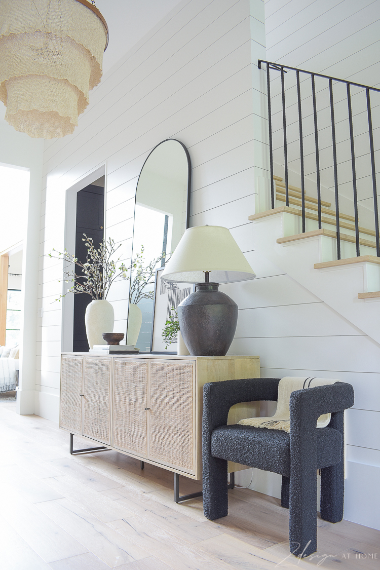 boucle chair styled next to cane console in entryway - upscale boho styling