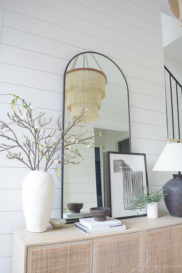 large arched floor mirror and decor on cane console table