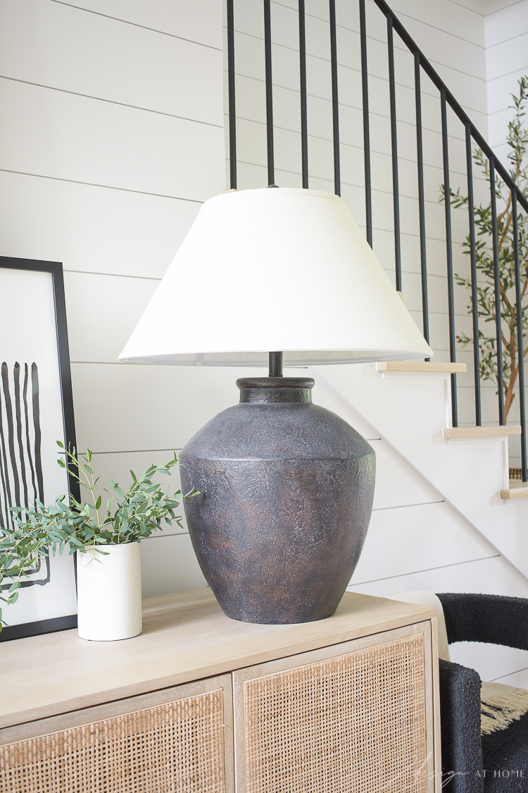 Black boho lamp styled on console table in entry