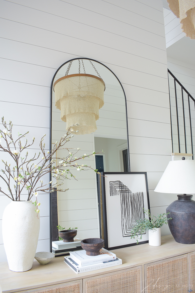 chandelier reflecting in mirror on console table - entryway