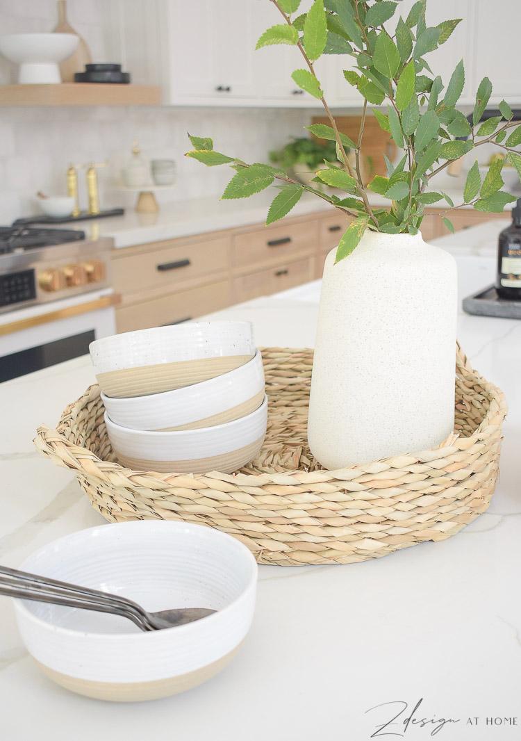 stoneware bowls, round rattan tray, speckled vase on kitchen island