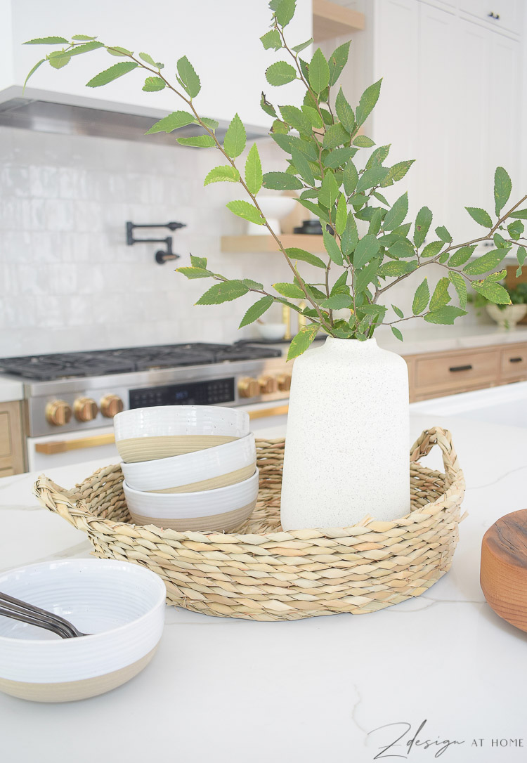 rattan tray with bowls and vase on kitchen island