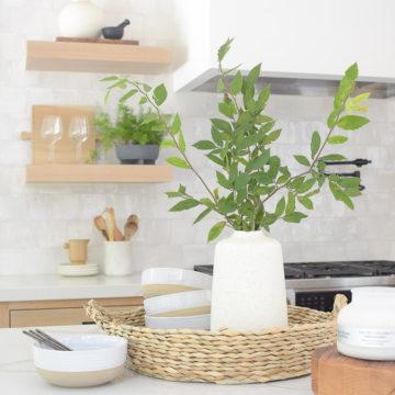 Walmart summer kitchen decor, walmart finds, white kitchen with white oak shelves, zellige tile and quartz countertops. How to style decorate kitchen island