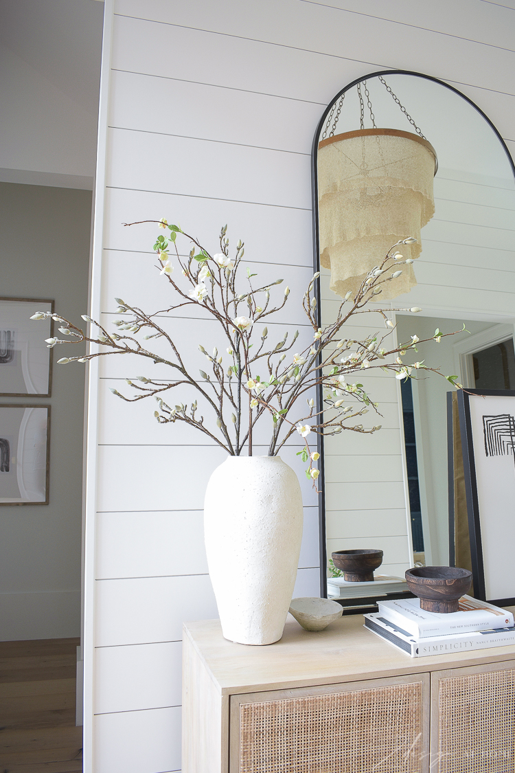 vase with faux quince and magnolia bloom stems