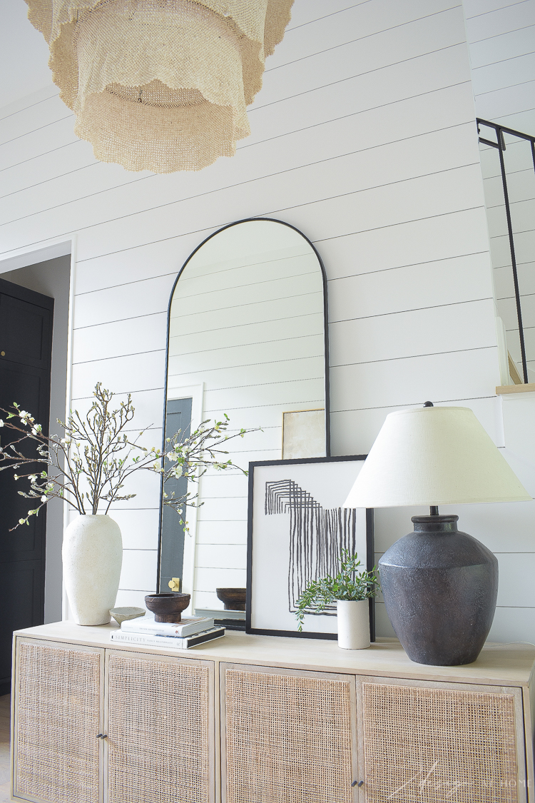 cane console buffet styled with modern boho home decor and black lamp