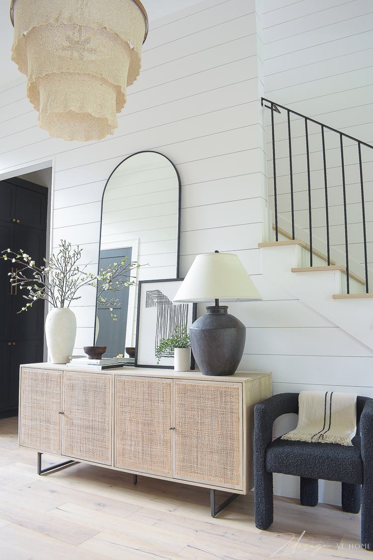 entryway hall with cane console table decorated with large mirror, art and decor