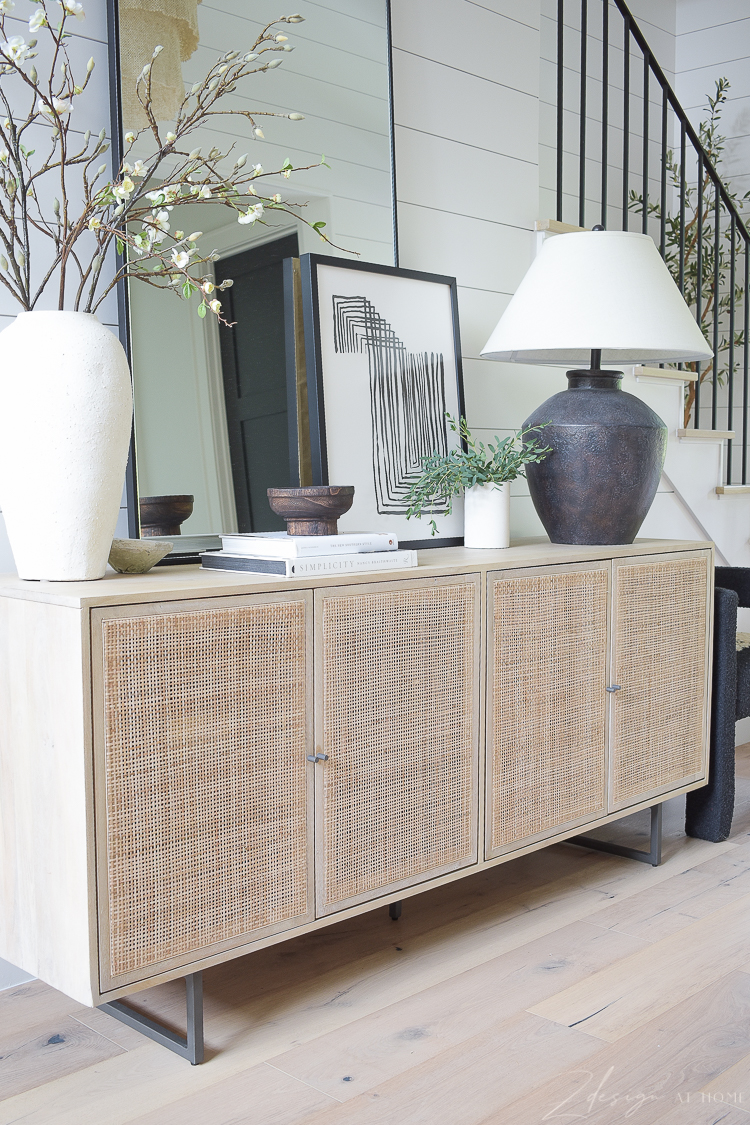 Cane console table in entry way with mirror and decor