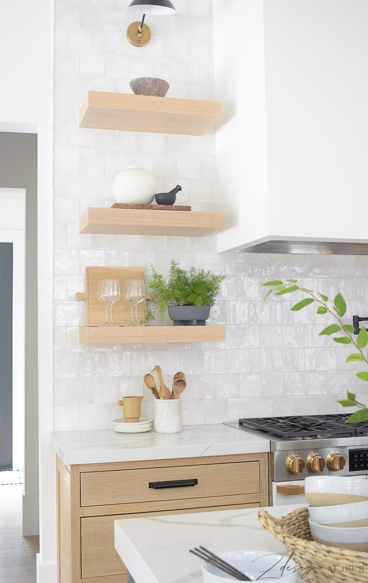 white oak open shelves in the kitchen with white zellige backsplash