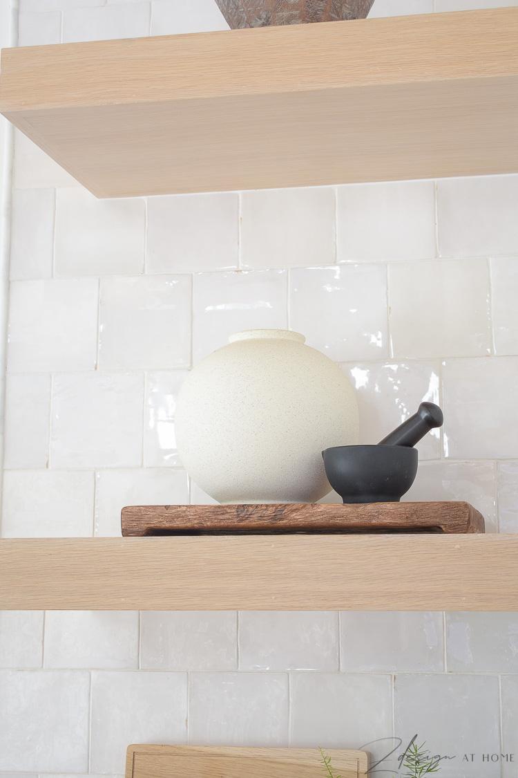 white speckled vase styled on open white oak kitchen shelves