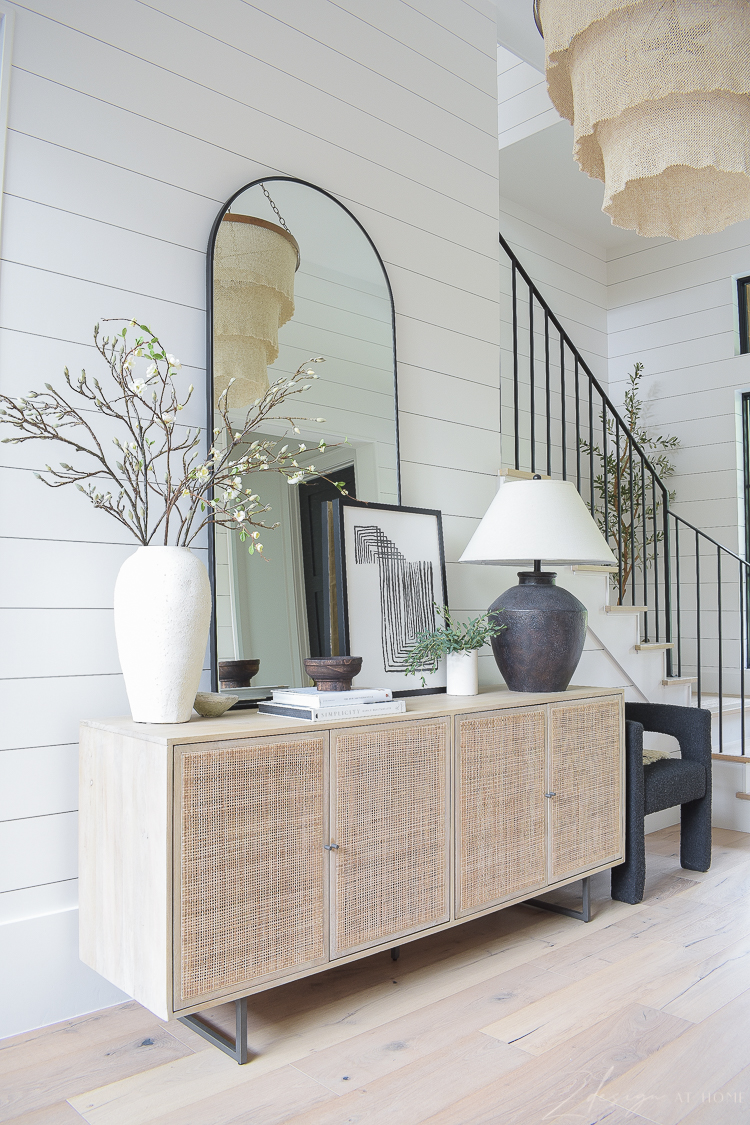 cane console with arched mirror and decor in entryway