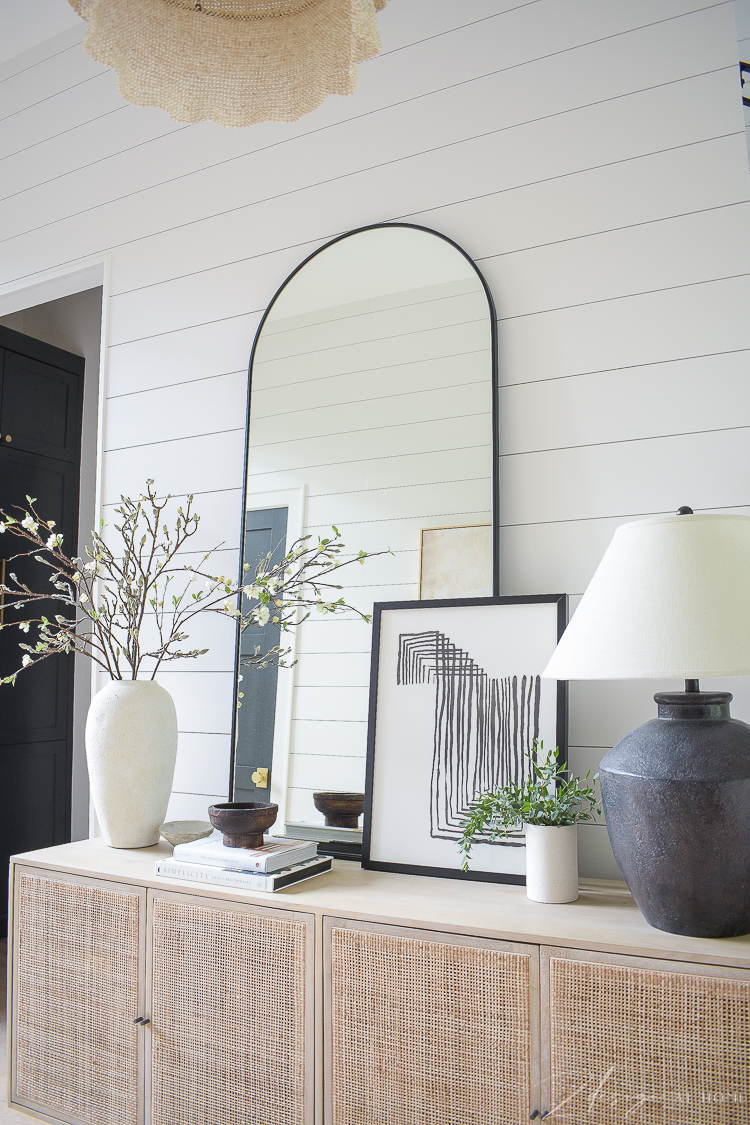Cane console with large floor mirror and decor atop