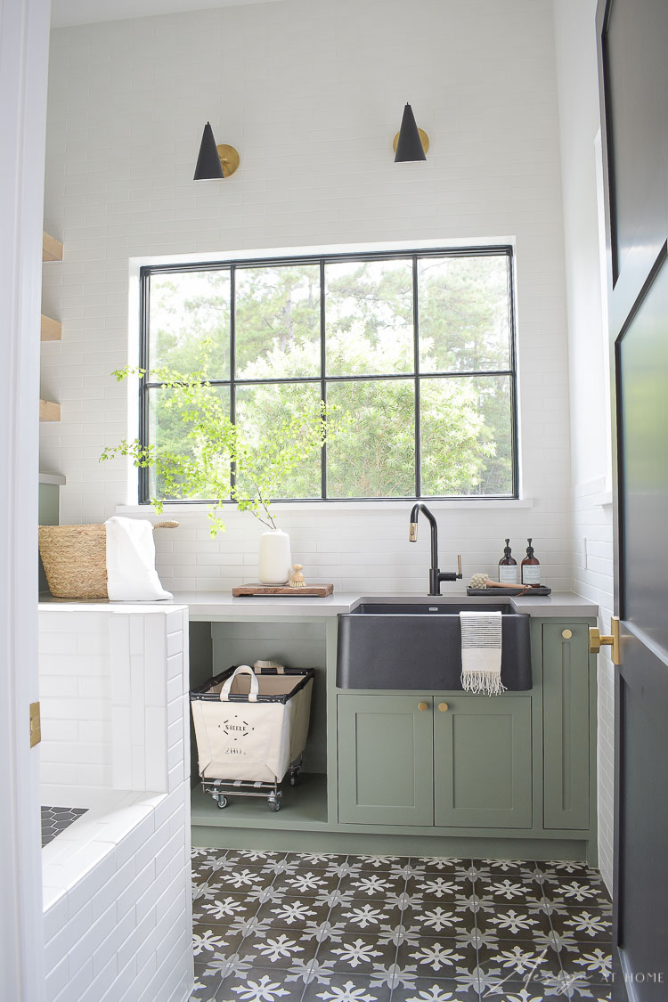 gorgeous laundry room with gray green cabinets and black floors patterned