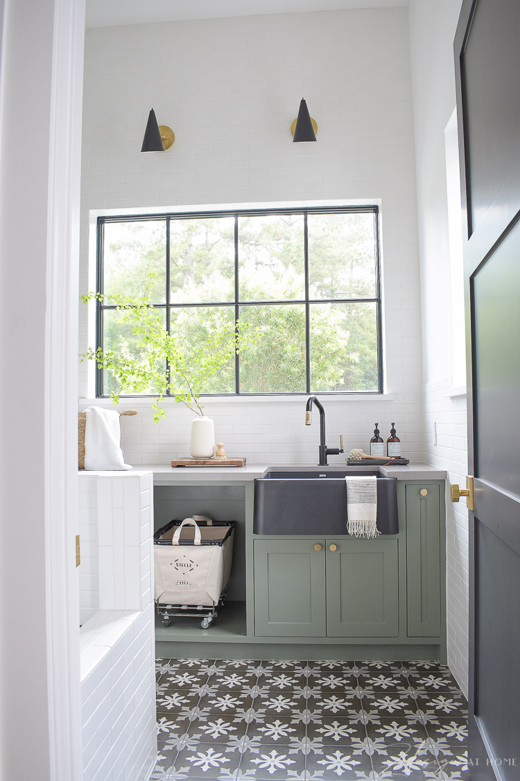 gorgeous laundry room with black white patterned tile floor and gray green cabinets