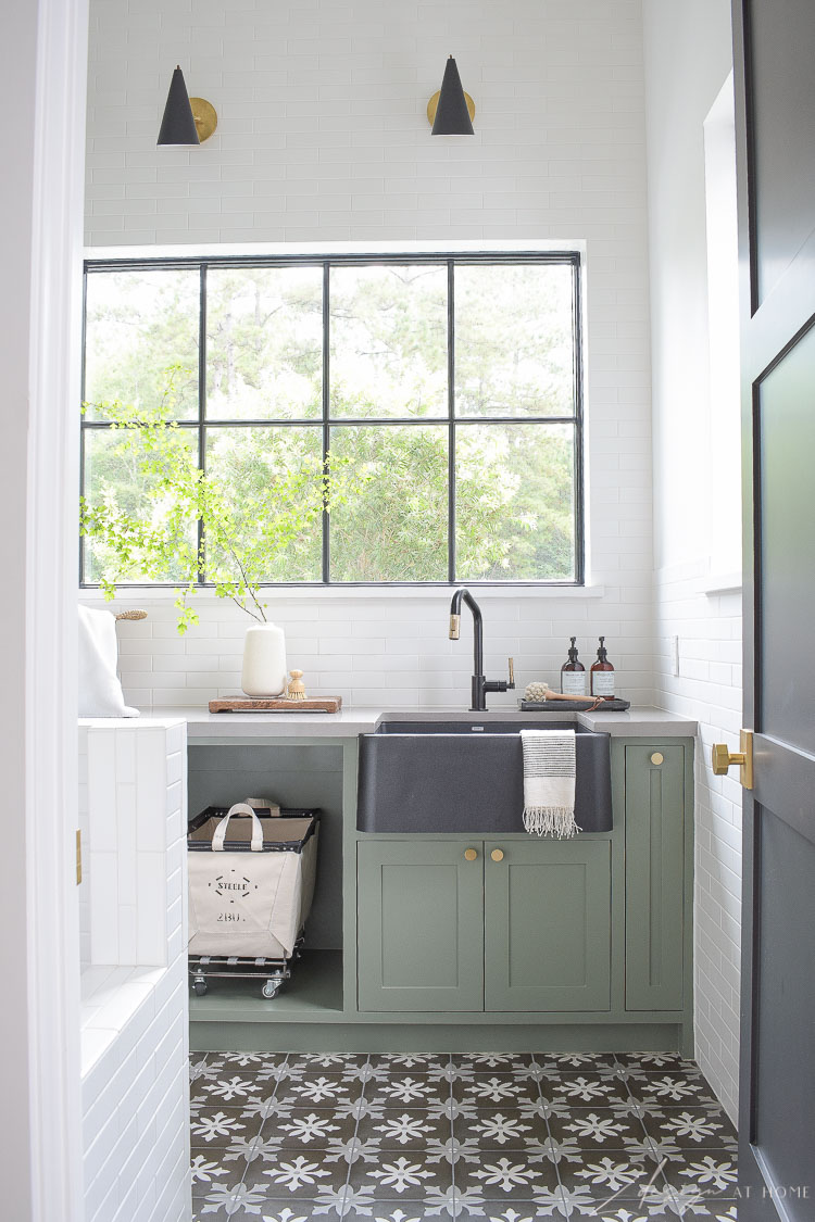 gorgeous black and white laundry room with gray green cabinets and pattern tile floors
