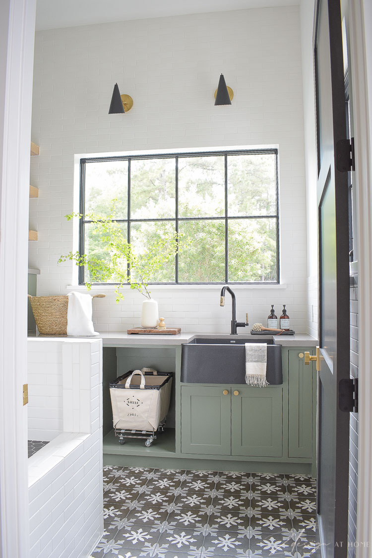 beautiful laundry room with gray green cabinets and tile to ceiling