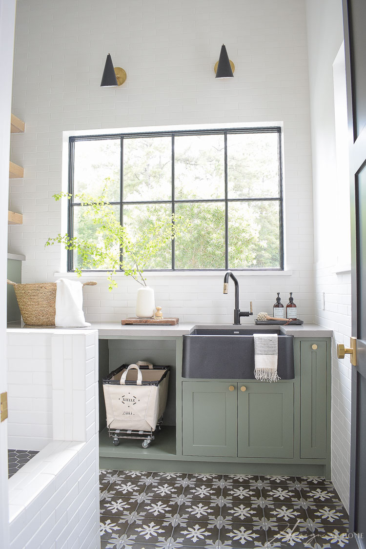 elegant laundry room with gray green cabinets and light pouring in